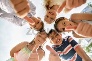 happy children showing thumbs up in circle