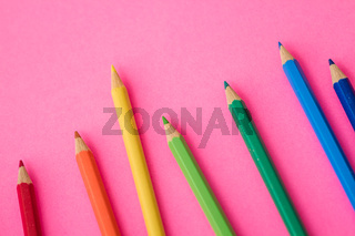 Bunch of Colorful Pencils Scattered on Pink Background