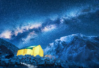 Milky Way, yellow glowing tent and mountains. Space