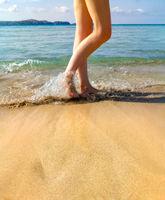 Beautiful woman legs, walking on the beach
