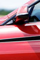 Detail on hot red sport car - side rearview mirror