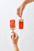 Creative food composition of a fruit ice cream in a female hand and a juicy piece of watermelon on a stick holds a male hand on a gray background space for text. Summer dessert