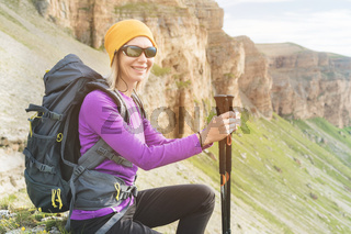 Smiling girl traveler in a yellow hat and a pair of sunglasses ssitting at the foot of epic rocks with a backpack next and looks in camera