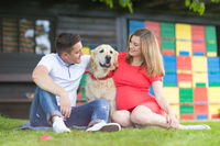 A Young couple expecting baby with their Golden retriever dog