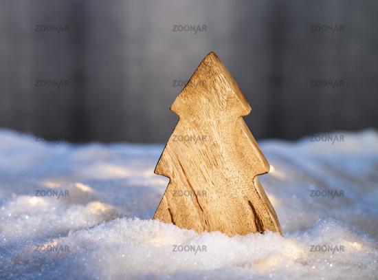 Hölzerner Weihnachtsbaum in Schneelandschaft