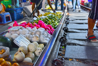 Selling food on the Maeklong Railway market in Thailand.