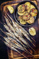Traditional Spanish barbecue sardines on a wooden skewer with fries as top view on a cutting board