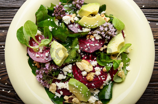 Top view at mediterranean roasted beet salad with avocado walnuts feta cheese oregano and mash leaves on wooden table