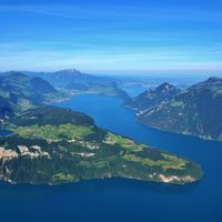 View from Mount Fronalpstock. Lake Lucerne in summer. Green meadows and mountains. Village Seelisberg.