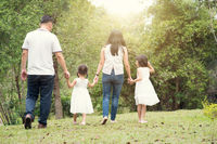 Asian family hold hands and walking at outdoor park, back view.