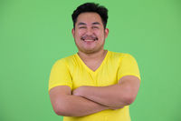 Happy young overweight Asian man smiling with arms crossed
