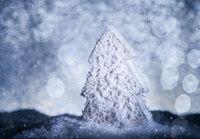 Weihnachtsbaum mit Schnee in blauem Licht