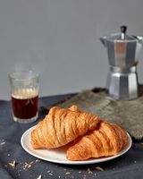 Morning breakfast with croissant and coffee on a gray background.