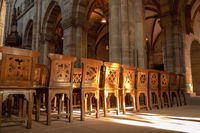 a row of wooden chairs in an old church