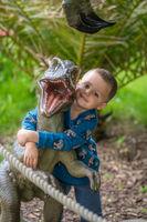 Boy hugging reptor dinosaur figure