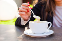 Business woman holding cup of cappuchino on outdoors cafe, close up