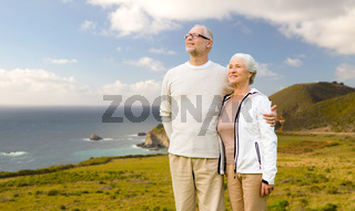 happy senior couple hugging over big sur coast