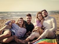 Group of friends having fun on beach during autumn day