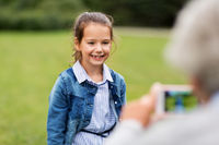 little girl being photographed at summer park
