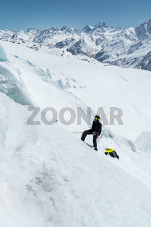 A professional mountaineer in a helmet and ski mask on the insurance does notch the ice ax in the glacier. The work of a professional climber in winter on a glacier against the blue sky