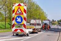 Road works with trucks and traffic signs
