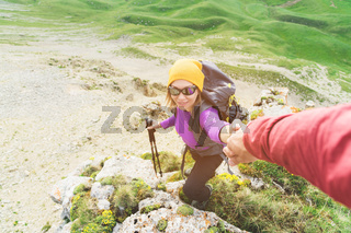 A climber helps a young mountaineer woman reach the top of the mountain. A man gives a helping hand to a woman. View from above