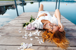 Attractive young hipster woman in white dress lies on the wooden floor.