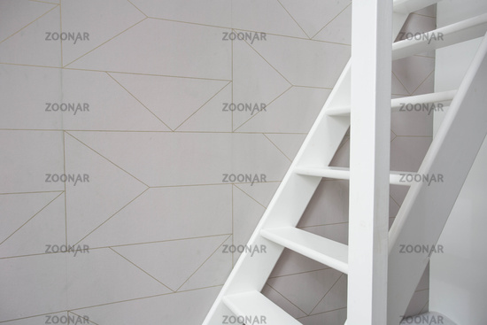 Stairs in modern white room, white wooden stairs with white wall retro wallpaper