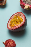 Half of passion fruit with litchi and dragon fruit on a blue background