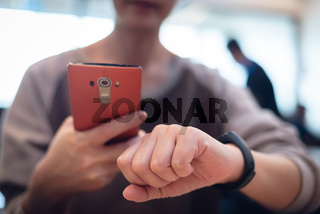 woman using smart watch and cellphone