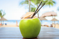Coconut with cocktail drinking straw in front of tropical sea background