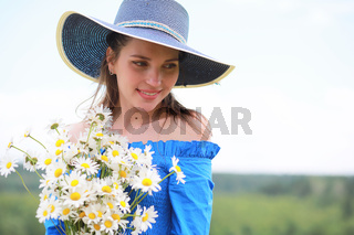 Young cute girl in a hat in a field at sunset
