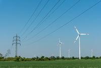 Freileitungen und Windkraftanlagen vor blauem Himmel