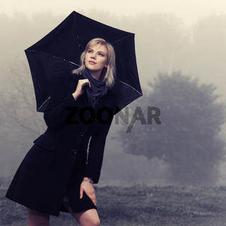 Young fashion woman with umbrella walking in a fog outdoors