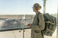 Casually dressed female traveler at airport, holding smart phone device, looking through the airport gate windows at planes on airport runway