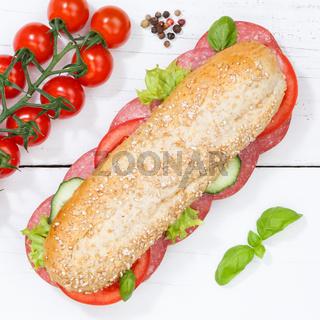 Sandwich Baguette Vollkorn Brötchen belegt mit Salami Quadrat von oben auf Holzbrett