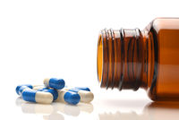 A prescription bottle on its side with blue and whiite capsules spilling out