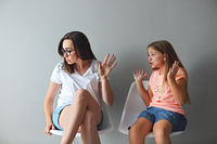 Furious young mother in a discussion with her teenage daughter