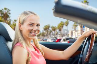woman driving convertible car over venice beach