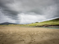 Sandy beach with dunes and dark stormy clouds