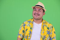 Face of happy young overweight Asian tourist man thinking