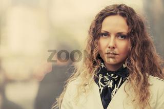 Beautiful fashion woman in white trench coat walking in city street