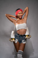 Young beautiful Asian girl with retro quads roller skates isolated over concrete wall