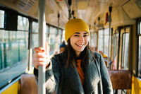 Young woman standing in a wagon of a driving tramway. Transportation, travel and lifestyle concept.