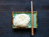 rice and chopsticks on green plate on dark board