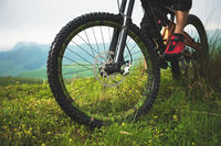 Close-up of a mountain bike wheel in the mountains on the green grass and foot of a rider