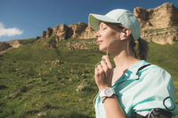 Fitness runner woman closing his eyes listening to music on the nature. Portrait of beautiful girl wearing earphones earbuds and running cap. against the background of rocks field and blue sky