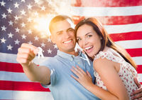 Military Couple Holding House Keys In Front of American Flag
