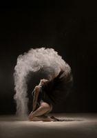 Brunette on her knees in white dust cloud
