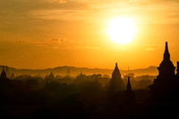 Early morning bright golden sun silhouettes ancient pagodas and temples of Bagan, Myanmar.
